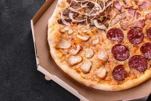 délicieuse pizza fraîche préparée dans un four à sole avec quatre types de viande et de saucisse photo