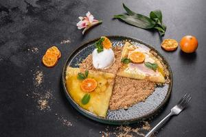 délicieuses crêpes fraîches sur une assiette avec sauce sucrée et crème glacée décorée de menthe photo