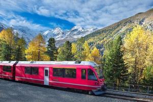 Le train de montagne suisse bernina express a traversé les alpes en automne photo