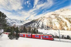passe de train rouge touristique de la Bernina sur les alpes suisses photo