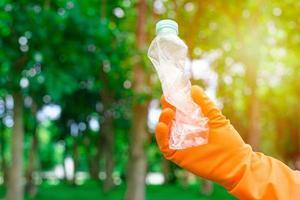 la main de l'homme bénévole ramassant une bouteille en plastique photo