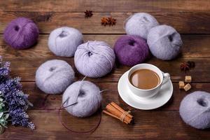 enchevêtrements de fils de laine et de rayons avec une tasse de café et de sucre sur un fond en bois photo