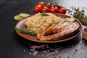 délicieux steak de saumon frais cuit avec des épices et des herbes cuites sur un gril photo