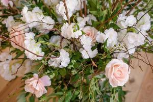 décorations de branches avec de belles fleurs roses et blanches dans le panier sur fond de mur de briques blanches photo