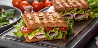 délicieux sandwich avec des toasts croustillants, du jambon, de la laitue et des tomates photo
