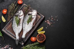 poisson dorado cru aux épices cuisant sur une planche à découper. daurade de poisson frais photo