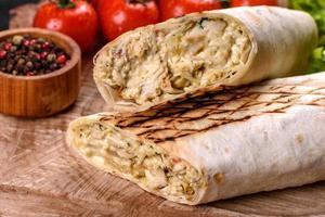 délicieux shawarma frais avec de la viande et des légumes sur une table en béton foncé photo