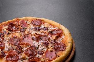 délicieuse pizza fraîche au four avec tomates, salami et bacon sur fond de béton foncé photo