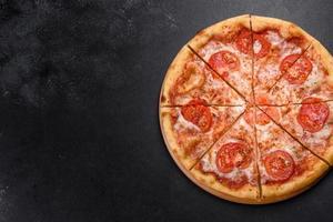 savoureuse pizza au four frais avec tomates, fromage et basilic sur fond de béton photo