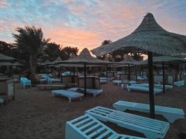 chaises longues et parasols en paille et beau coucher de soleil sur la plage d'hurghada, égypte photo