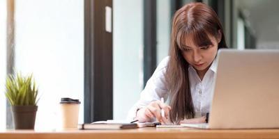 portrait d'une jolie jeune femme étudiant assis à la table photo