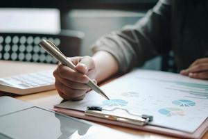 homme d'affaires tenant un stylo et pointant sur des documents financiers photo