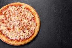 savoureuse pizza au four frais avec tomates, fromage et ananas sur fond de béton foncé photo