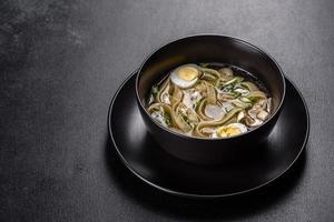 délicieuse soupe chaude fraîche avec nouilles et œuf de caille dans une assiette noire photo