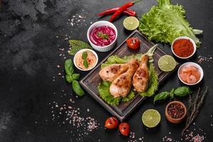 cuisses de poulet grillées savoureuses avec des épices et des herbes sur une planche de bois sur fond de béton foncé photo