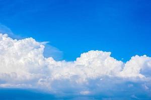 beaux nuages blancs dans un ciel bleu vif par une chaude journée d'été photo