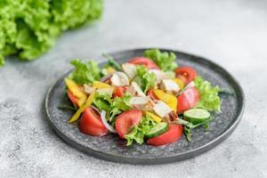 délicieuse salade fraîche avec poulet, tomate, concombre, oignons et légumes verts à l'huile d'olive photo
