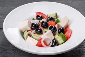 délicieuse salade grecque fraîche avec tomate, concombre, oignons et olives à l'huile d'olive photo