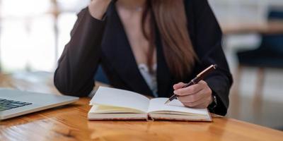 gros plan sur les mains de la femme avec un ordinateur portable, un ordinateur portable et un stylo photo