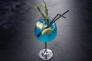 cocktail alcoolisé curaçao bleu avec glace, citron et tubes à cocktail photo