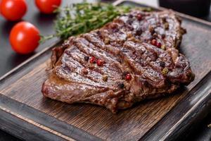 délicieux steak de boeuf frais juteux avec des épices et des herbes sur un fond de béton foncé photo