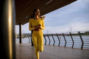 jeune femme prenant l'exercice de course par la promenade de la rivière photo