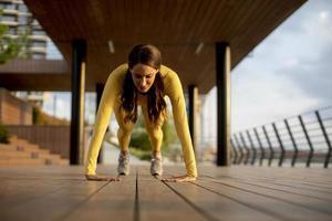 Jeune femme effectuant des pompes à passerelle en bois au bord de la rivière photo