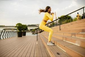 Jeune femme sautant dans les escaliers au bord de la rivière photo