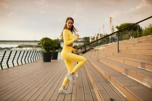 jeune femme prenant des exercices sur les escaliers par la promenade de la rivière photo