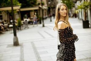 Jeune femme brune aux cheveux longs marchant dans la rue photo