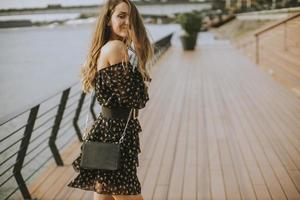 Jeune femme brune aux cheveux longs marchant au bord de la rivière photo