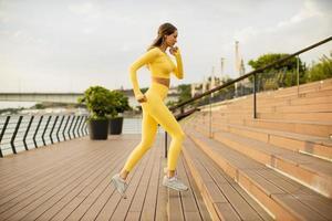 Jeune femme qui court dans les escaliers au bord de la rivière photo