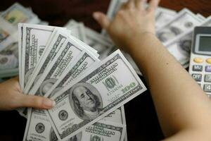 hommes d'affaires femmes comptant de l'argent sur une pile de billets de 100 dollars américains beaucoup d'argent photo