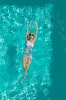 jeune belle fille sexy appréciant nager dans la piscine privée et se détendre au soleil photo