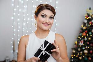 tournage de noël. beau modèle avec des cadeaux du nouvel an sur fond d'arbre de noël. photo