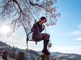 une jeune fille se balance sur une balançoire. journée ensoleillée. photo