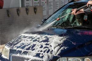 voiture sans contact lavage en libre-service. laver avec de l'eau et de la mousse. photo