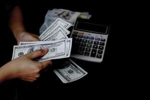 Les femmes comptent de l'argent sur une pile de billets de 100 dollars américains beaucoup d'argent photo