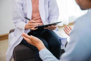 psychologue professionnelle femme effectuant une consultation et parler avec un patient asiatique photo