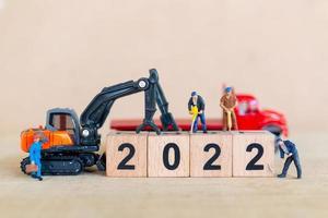 Une équipe de travailleurs miniature crée un bloc de bois numéro 2022 photo