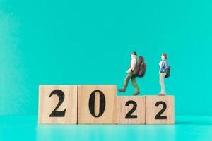 Backpacker miniature et touriste debout sur un bloc de bois numéro 2022 photo