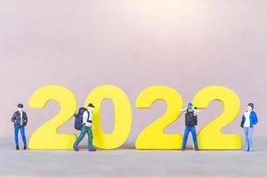 Backpacker de personnes miniatures debout sur le numéro en bois 2022 photo