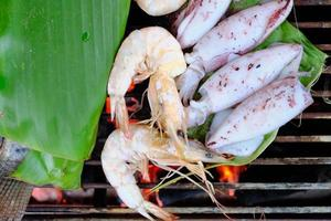 les fruits de mer frais tels que les crevettes, les calmars et les poissons sont traditionnellement rôtis par des feuilles de bananier enveloppées sur un barbecue au charbon de bois fumé. c'est un délicieux dîner pour les barbecues, les pique-niques ou les repas au restaurant. photo