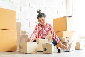 femme asiatique propriétaire d'entreprise travaillant à la maison avec une boîte d'emballage sur le lieu de travail - achat en ligne PME entrepreneur ou concept de travail indépendant photo