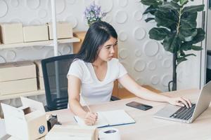 jeune femme asiatique propriétaire d'une petite entreprise travaillant avec une tablette numérique sur le lieu de travail - vente en ligne, commerce électronique, concept d'expédition photo