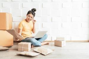 jeune entreprise asiatique démarre le propriétaire d'un vendeur en ligne à l'aide d'un ordinateur pour vérifier les commandes des clients à partir d'un courrier électronique ou d'un site Web et préparer des colis - achats en ligne ou concept de vente en ligne photo