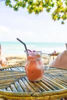 mangue, ananas, pastèque et pot de smoothies au yaourt ou au yaourt avec fond de plage de mer photo