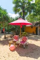 Parapluie rose et chaise sur la plage tropicale photo