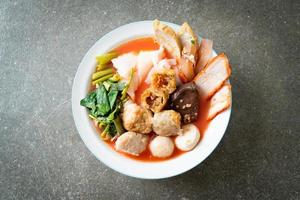 nouilles aux boulettes de viande dans une soupe rose ou yen ta quatre nouilles à l'asiatique photo
