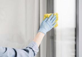 femme avec un gant en caoutchouc essuyant la fenêtre. beau concept de photo de haute qualité